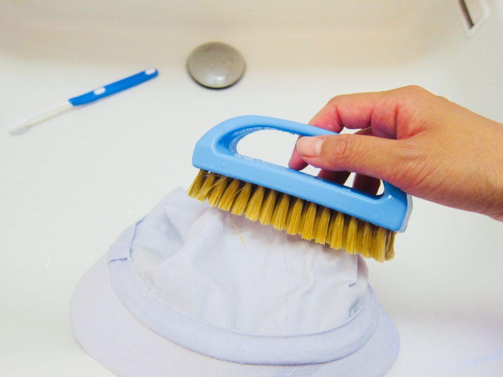 帽子を洗濯ブラシで洗う