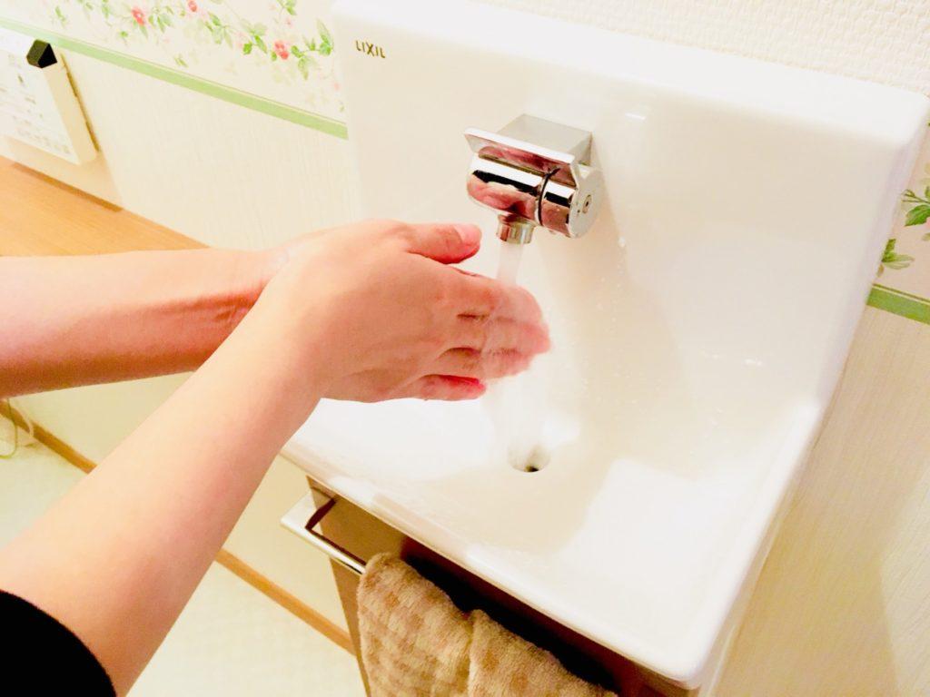 トイレの手洗い器で手を洗っている